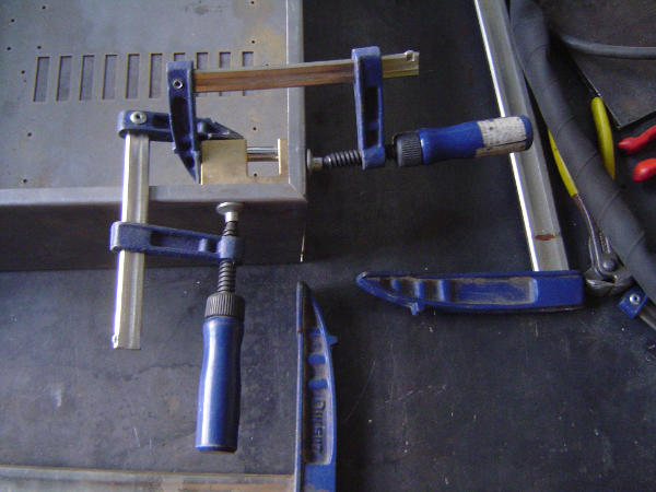 Two clamps holding a brass piece at a corner